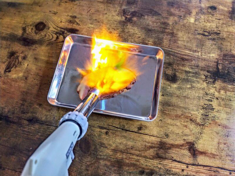 トッピング用のチャーシューをバーナーで炙っている写真