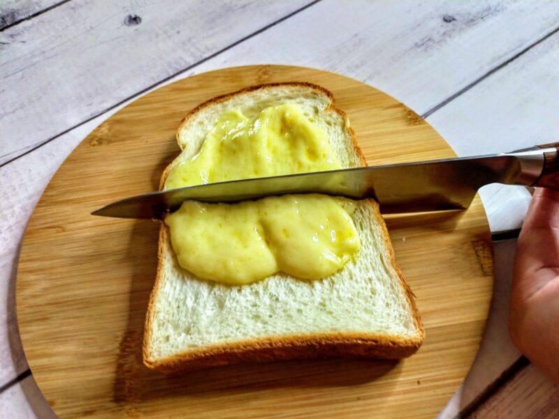 チーズをのせたパンを2つに切る